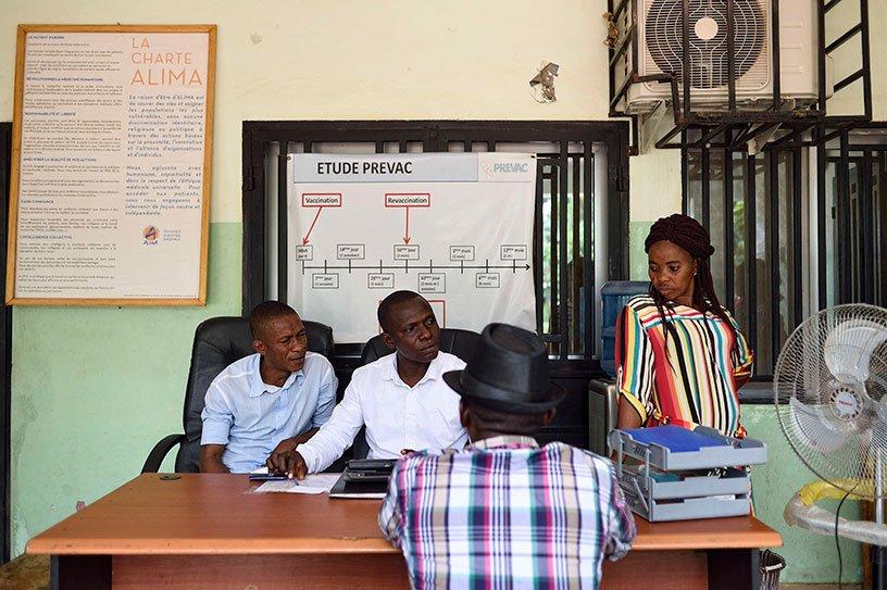 Quatre personnes assises de part et d'autre d'un bureau