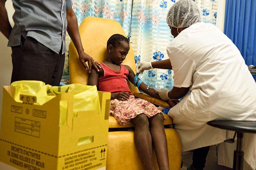 Une infirmière pose une aiguille dans le bras d'une petite fille pour une prise de sang