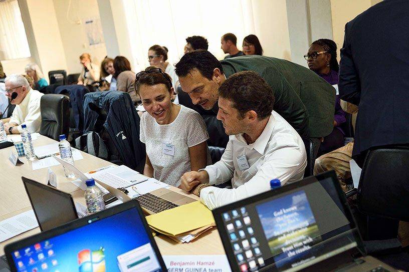 Trois personnes discutent autour d'un ordinateur