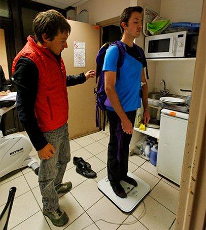 Un des investigateurs de l'étude, évalue l'équilibre postural du volontaire grâce à une plateforme de force