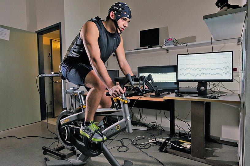 Un volontaire réalise un test d'effort sur vélo, il porte un bonnet EEG