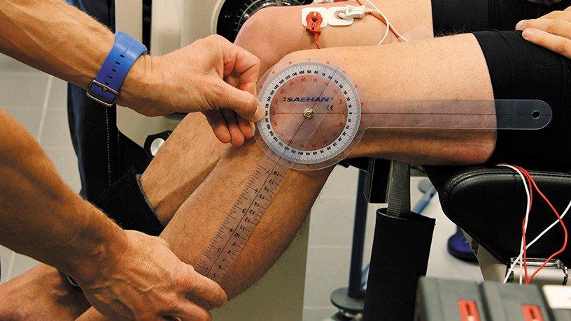 Evaluation de la fonction neuromusculaire en laboratoire sur un sujet volontaire, un angle précis est appliqué à l'articulation au niveau du genou pour enregistrer via des électrodes sur la cuisse.